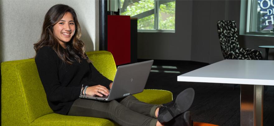 Lauren Kotz sitting on a bench working on her computer