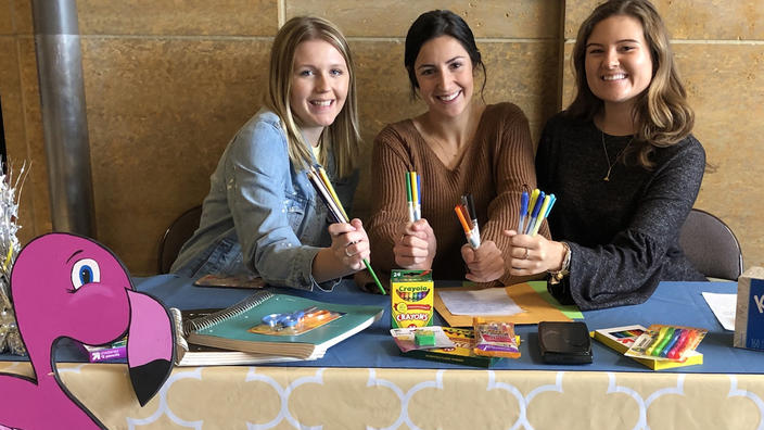 Abbey DeGoey and two members of Phi Sigma Sigma with school supplies.