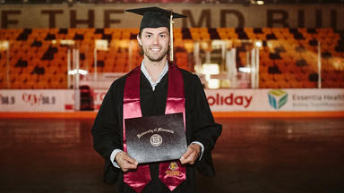 Rob Bordson holding diploma at AMSOIL Arena