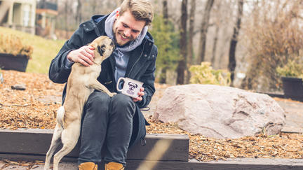 Benji with a pug dog and a cup.