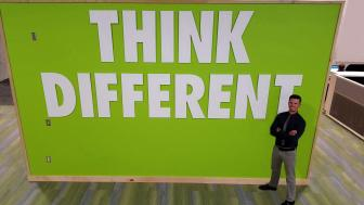 "Eli Kohorst in front of ""Think Different"" sign"