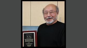 Dr. Shee Wong with a plaque