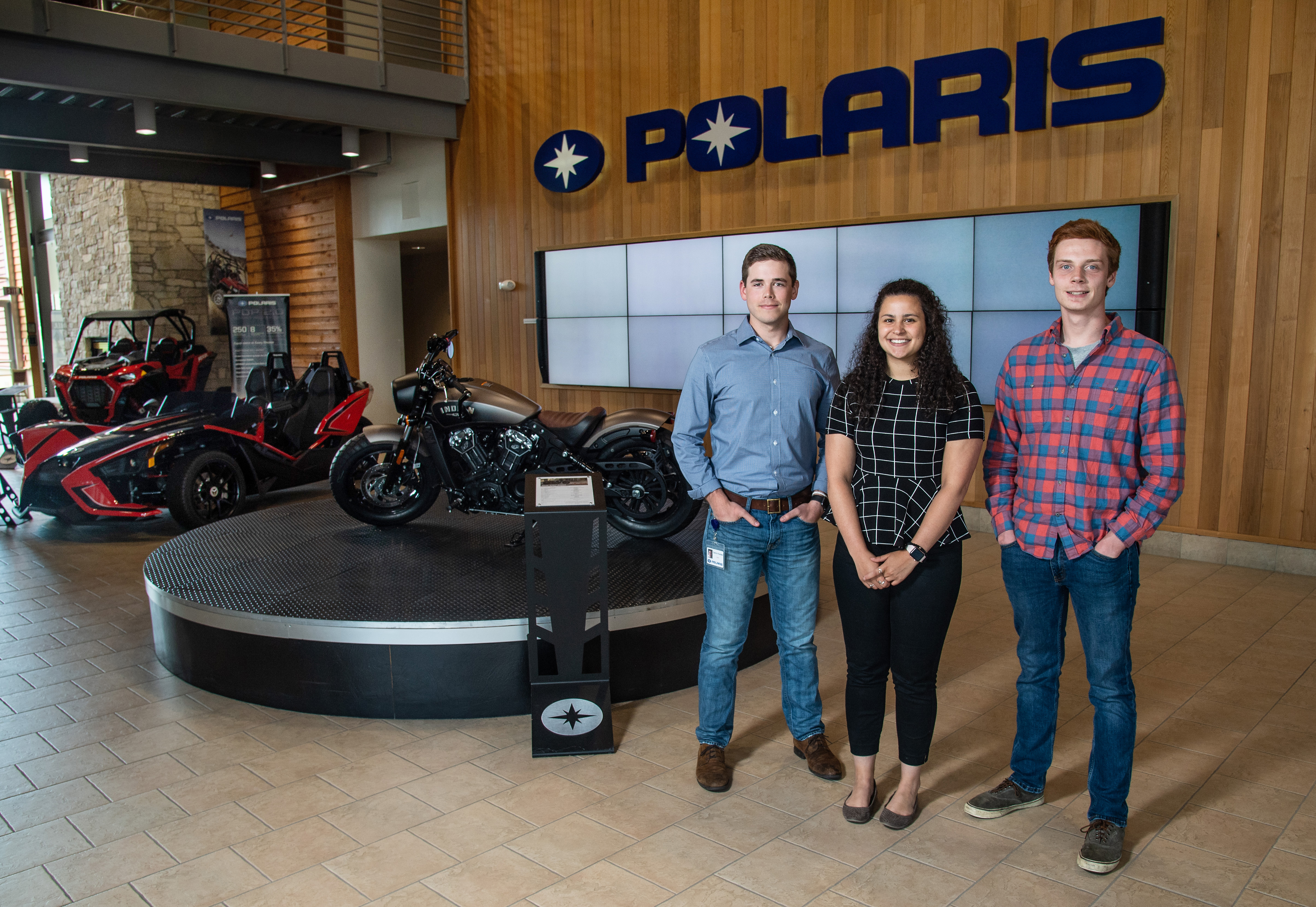 Three interns in front of Polaris sign